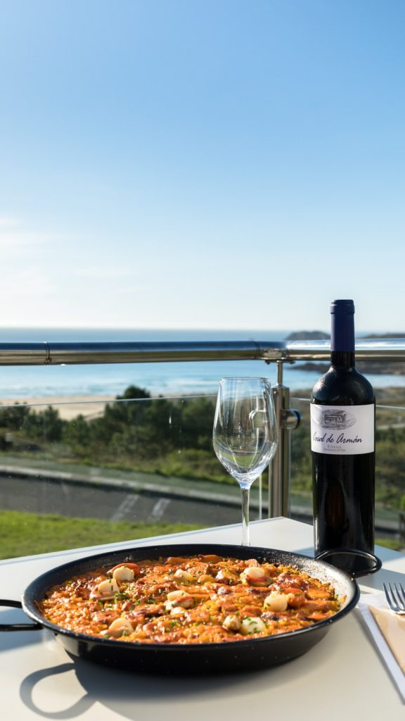 Arroz de marisco y verduritas en la terraza de Valverde New, la playa de Doniños al fondo